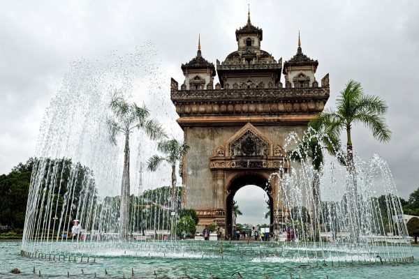 The Patuxai, a monumental arch sits behind a fountain in Vientiane, Laos.
