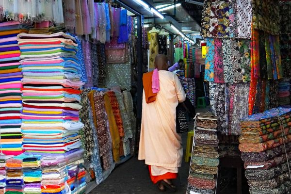 A Buddhist nun shops for cloth at the Bogyoke Aung San Market in Yangon, Myanmar. She wears a pale orange robe and her head is shaved. To either side of her are displays of cloth in different colors and styles..