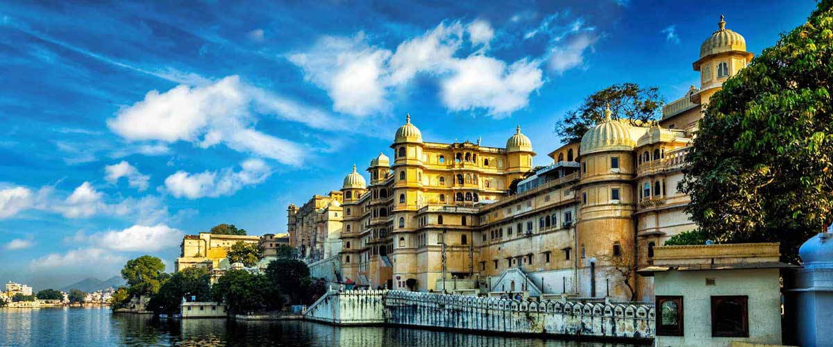The Udaipur City Palace, India, golden yellow buildings along Lake Pichola.