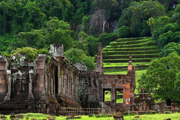 The ruins of the ancient Vat Phou temple, in southern Laos, at the foot of a terraced rice padi.
